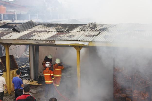 Pekanbaru indonesien 1. august 2015 feuerwehrleute versuchen, ein feuer zu löschen, das eine gemeinde verschlingt