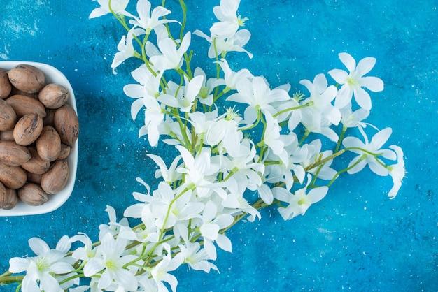 Pekannüsse in einer schüssel neben blumen, auf dem blauen tisch.