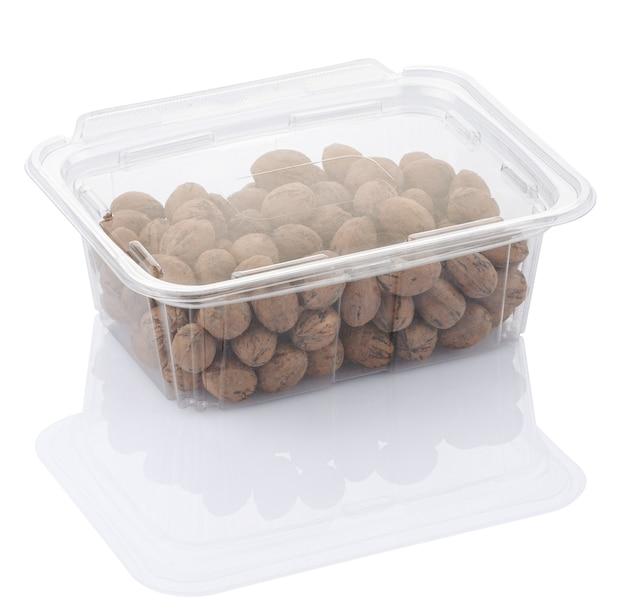 Pekannüsse in einer transparenten plastiknahrungsmittelbox, die mit beschneidungsweg isoliert wird