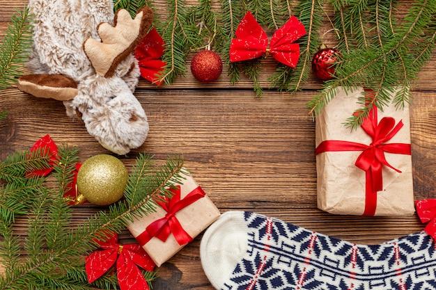 Pelz fichte nadelholz zweige, wollsocken, geschenkbox bastelpapier mit roter schleife, rotgold spielzeug kugeln elch, elch spielzeug