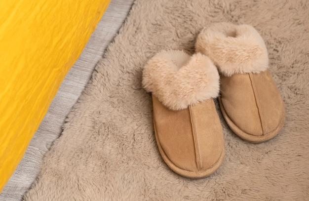 Pelzige weiche hausschuhe auf dem teppich neben dem bett.