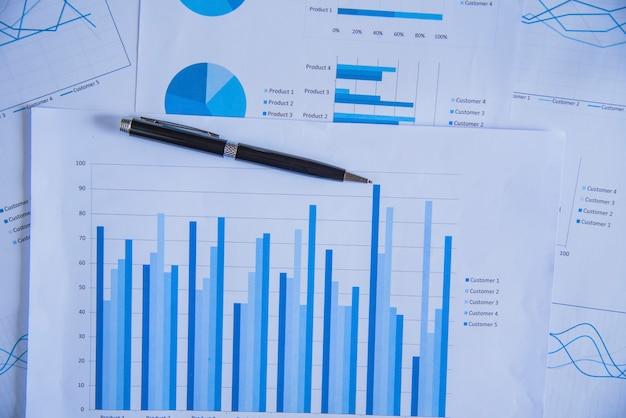 Pen auf diagramm diagramm und grafiken business report mit geld, kompass, taschenrechner auf schreibtisch von finanzberater. buchhaltungs- und finanzplanungskonzept draufsicht