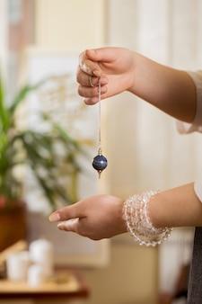 Pendel in den händen eines heilers