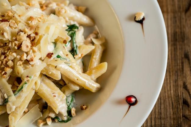 Penne mit huhn, spinat und haselnuss in parmesansauce
