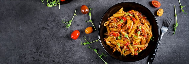 Penne nudeln in tomatensauce mit fleisch, tomaten mit erbsensprossen auf einem dunklen tisch dekoriert.
