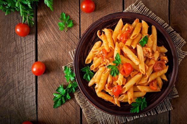 Penne nudeln in tomatensauce mit huhn und tomaten auf einem holztisch