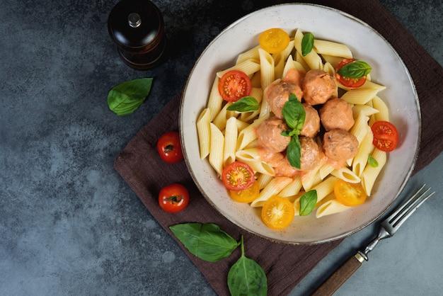 Penne nudeln mit fleischbällchen tomaten und sauce auf einem dunklen hintergrund, draufsicht