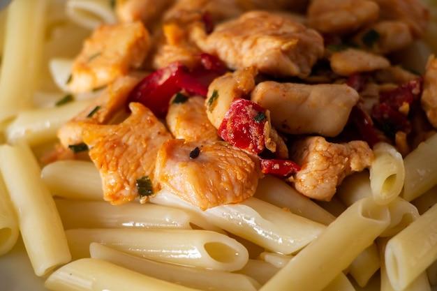 Penne-nudeln mit hühnchen und gemüse in tomatensauce.