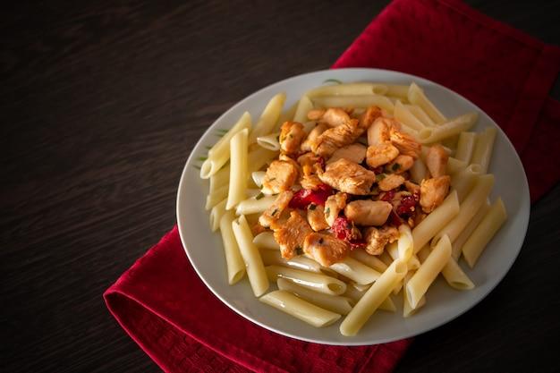 Penne-nudeln mit hühnerfleisch und gemüse in tomatensauce