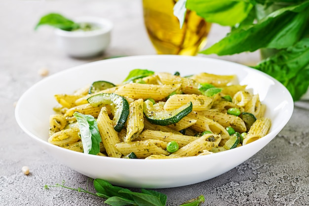 Penne nudeln mit pesto-sauce, zucchini, erbsen und basilikum. italienisches essen.