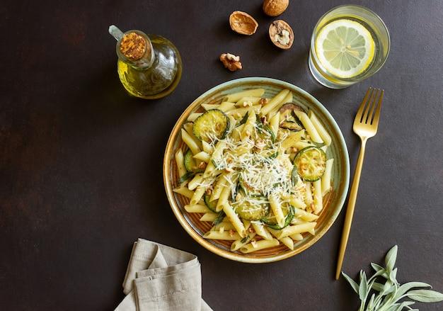 Penne-nudeln mit zucchini, salbei, nüssen und parmesan. gesundes essen. vegetarisches essen. italienisches essen.