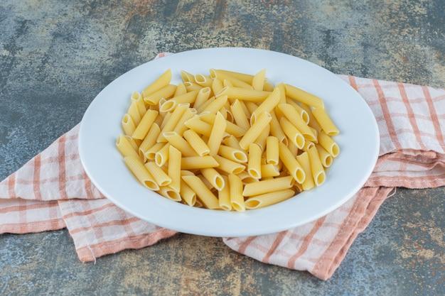 Penne pasta auf dem teller, auf dem handtuch, auf dem marmorhintergrund.