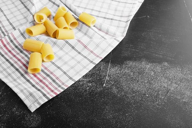 Penne pasta auf einem karierten küchentuch.