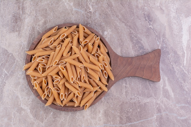 Penne pasta auf einer holzplatte auf dem marmor