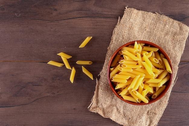 Penne pasta auf sackleinen draufsicht auf holzoberfläche