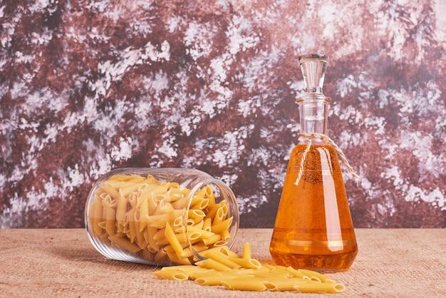 Penne pasta in einem glas mit einer flasche öl.