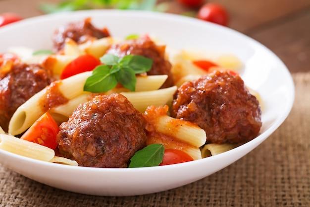 Penne pasta mit fleischbällchen in tomatensauce in einer weißen schüssel