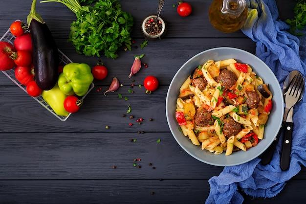 Penne pasta mit fleischbällchen in tomatensauce und gemüse in schüssel