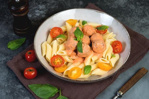 Penne pasta mit frikadellen tomaten und sauce auf einem dunklen hintergrund