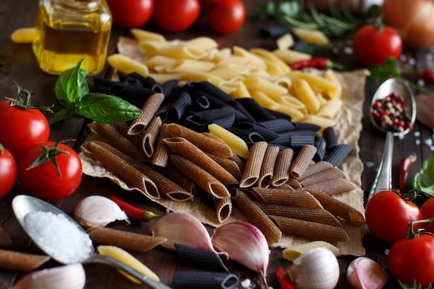Penne pasta mit gemüse, kräutern und olivenöl auf holztisch