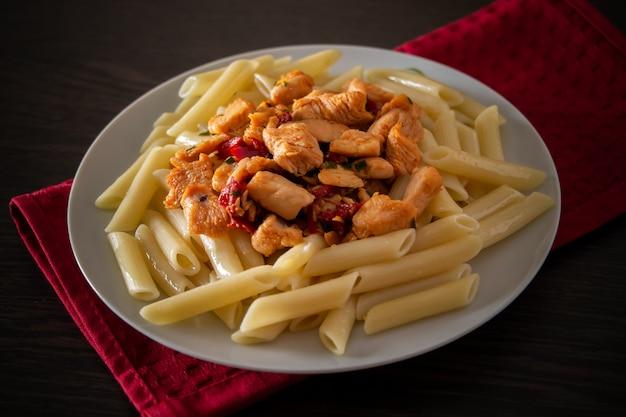 Penne pasta mit huhn und gemüse in tomatensauce
