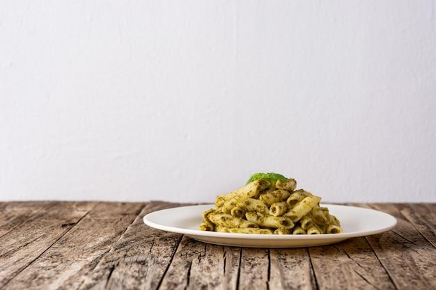 Penne pasta mit pesto-sauce auf holztisch