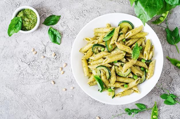 Penne pasta mit pesto-sauce, zucchini, erbsen und basilikum. italienisches essen. draufsicht. flach liegen.