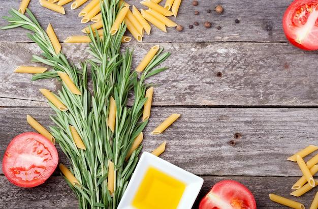 Penne pasta mit rosmarin, tomaten, olivenöl und pfeffer auf einem holztisch