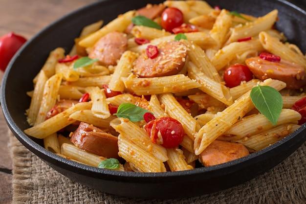 Penne pasta mit tomatensauce mit wurst, tomaten, grünem basilikum in einer pfanne auf einem holztisch dekoriert