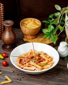 Penne pasta mit tomatensauce und paprika mit parmesanstreuseln