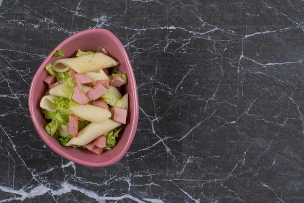 Penne pasta mit wurst und gemüse in rosa schüssel.