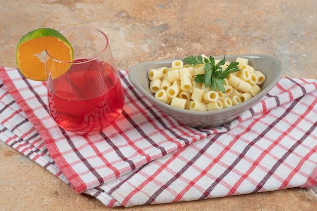 Penne pasta und glas roter cocktail auf tischdecke