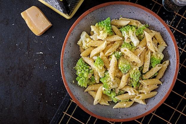 Penne-teigwaren mit kohl romanesco auf schwarzer tabelle. vegetarisches essen. italienisches menü draufsicht flach legen