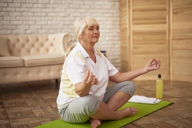 Pensionär-yoga-frau in lotus pose female health