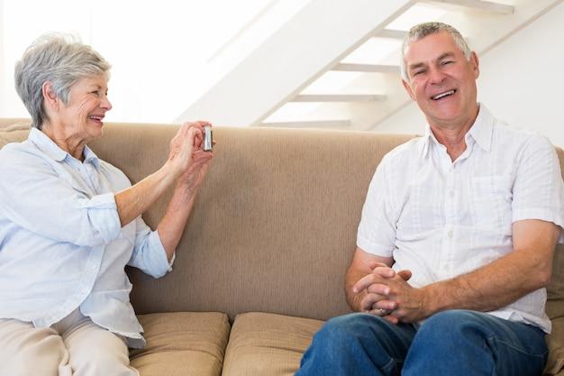 Pensionierte frau, die foto ihres partners auf der couch macht