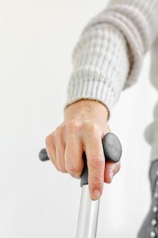 Pensionierte frau, die metallgehstock in der hand hält. medizin- und gesundheitskonzept.