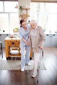 Pensionierte frau, die nach der operation schritte mit krücken macht
