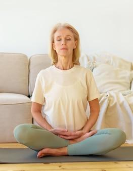 Pensionierte frau, die yoga meditiert und praktiziert, während sie in der lotuspose auf dem boden zu hause vertikal sitzt sitting