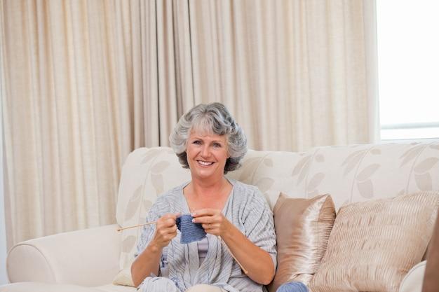 Pensionierte frau, die zu hause strickt