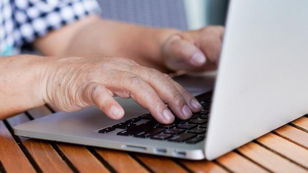 Pensionierte großmutterhand, die auf tastaturlaptop für das arbeiten schreibt