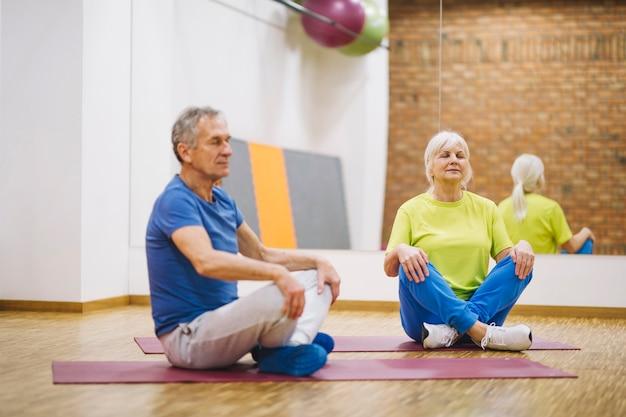 Pensionierte paare, die yoga tun