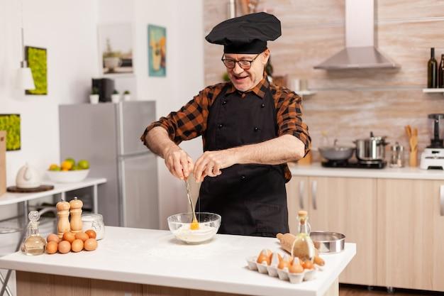 Pensionierter koch, der in der heimischen küche eier für weizenmehl knackt. älterer konditor, der ei auf glasschüssel für kuchenrezept in der küche knackt, von hand mischt, knetet.