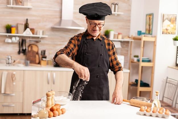 Pensionierter koch in der heimischen küche mit schürze, während er zutat auf den tisch streut, um lecker zu sein