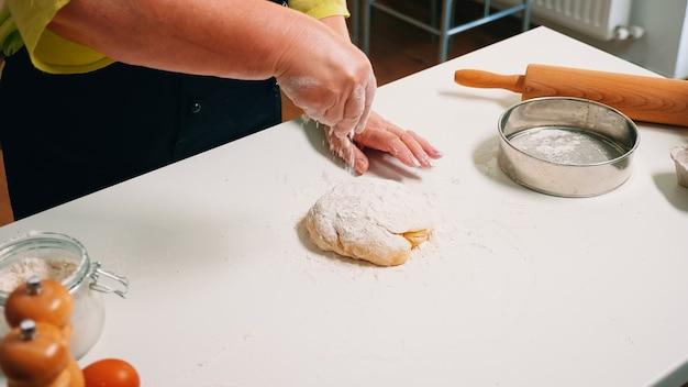 Pensionierter konditor, der zu hause in der küche auf holztisch mit weizenmehl kocht. älterer senior bäcker in einheitlicher besprengung, sieben, verteilen von zutaten auf dem teig, der hausgemachte pizza und brot backt