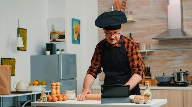 Pensionierter mann, der kulinarische ratschläge auf tablets befolgt, koch-tutorial in sozialen medien lernt, teig mit hölzernem nudelholz bildet. großvater mit bone und schürze mit laptop, der hauskuchen zubereitet