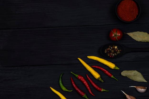 Peperoni, gewürze und gewürze liegen auf schwarzem holzhintergrund. platz für text. ansicht von oben.