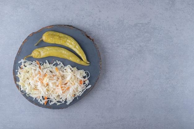 Peperoni mit sauerkraut an bord, auf dem marmorhintergrund.