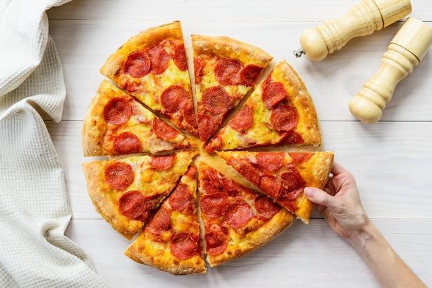 Peperoni-pizza auf einem hellen holztisch. die hand nimmt ein stück pizza.