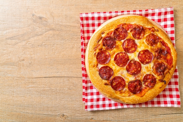 Peperoni-pizza auf holztablett - italienische küche