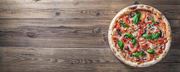 Peperoni-pizza mit jägerwürsten, pilzen, paprika und frischem basilikum auf einem holztisch